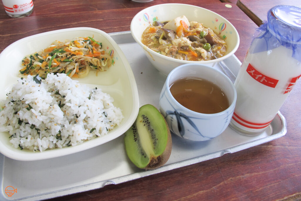 Seasoned rice with a side of vegetables. To the right is a vegetable, meat and tofu laden soup, half a kiwi fruit, a cup of hot hojicha tea and a bottle of cold milk.