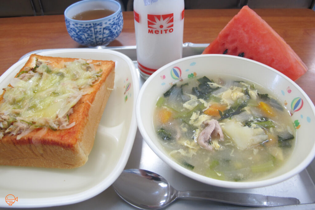 Hot soup with pork, seaweed and vegetables. To the left is a thick slice of bread with a tuna, vegetable and cheese topping. At the back is a big slice of watermelon, a bottle of milk and hot hojicha (Japanese roasted green tea).