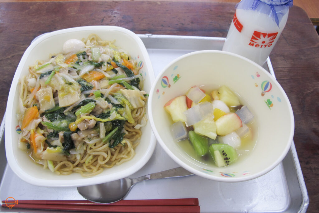 Noodles with a Chinese-style stir fry, including vegetables and quail egg. To the right is a bowl of fruit salad with apple, kiwi fruit and pineapple, along with mochi balls and almond jelly. Behind it is a bottle of milk.