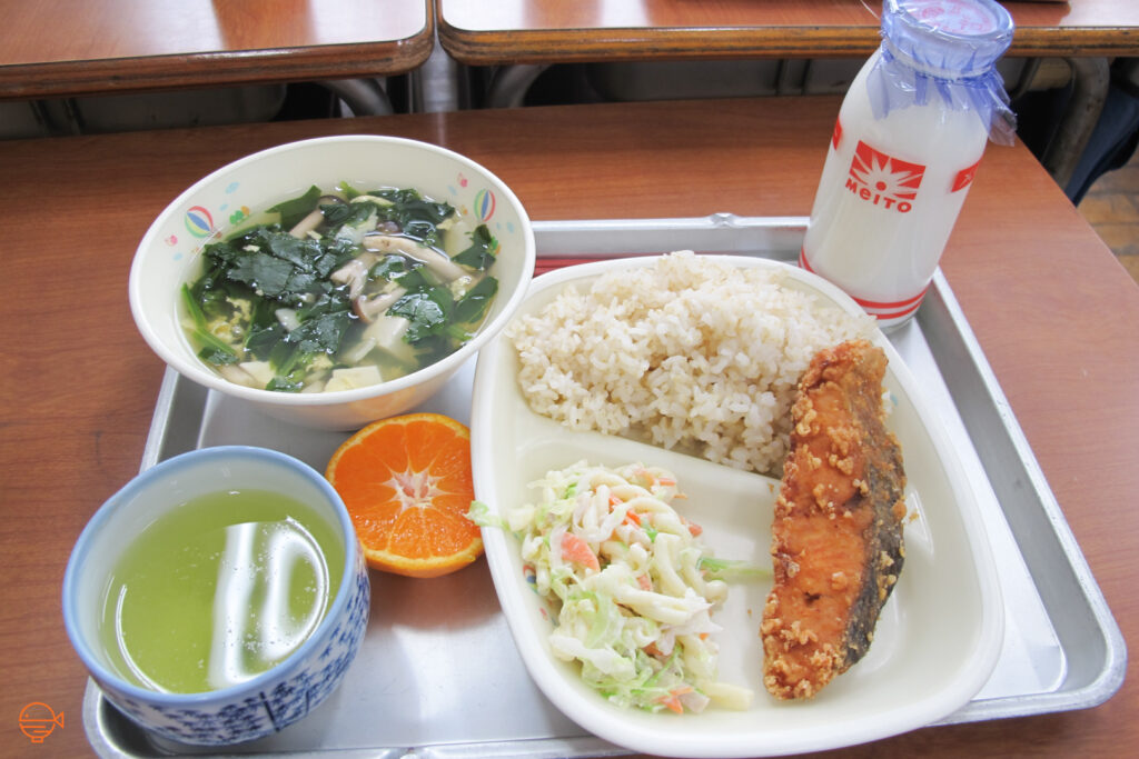 An ample serving of rice with a marinated piece of salmon and a cold side salad. To the left is a hot bowl of egg soup full of mushroom, tofu and seaweed, plus a cup of hot green tea and half an orange. To the right of the main dish is a bottle of milk.