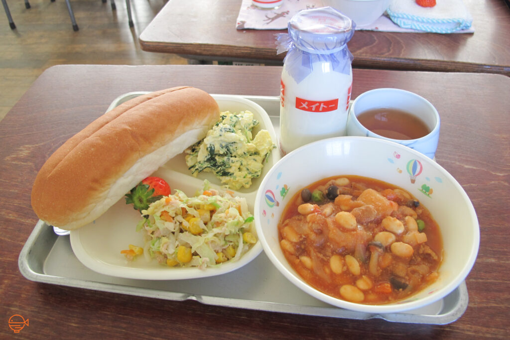 A hot dog style bun with an egg and vegetable filling to accompany. On the same plate is a cold salad and a strawberry. Next to it is a hot bowl of bean and vegetable tomato-based soup, as well as a hot cup of hojicha tea and a bottle of cold milk.
