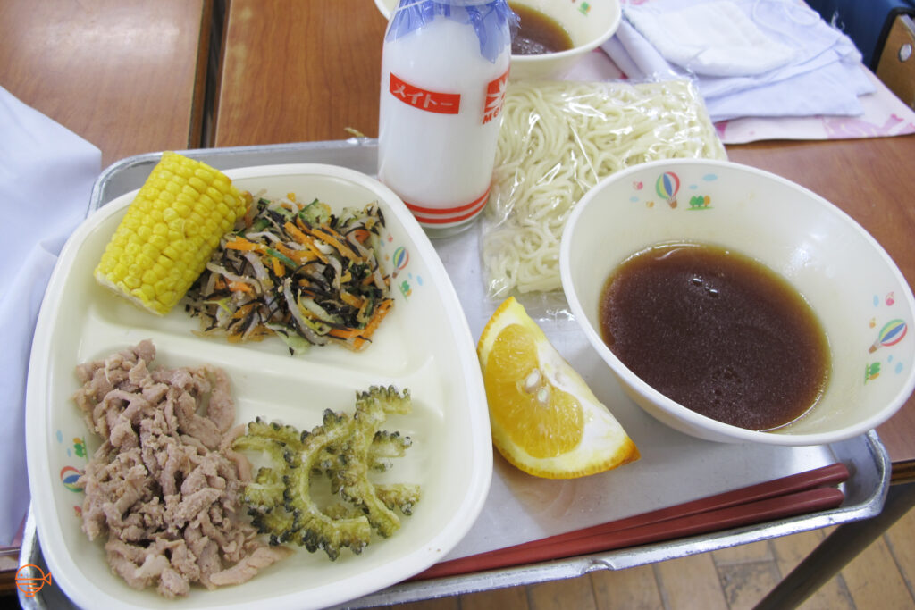 Half a cob of corn and a traditional Japanese pickled salad, along with a serving of pork and tempura bitter melon. To the right is a packet of noodles and a bowl of cold soy-sauce based dipping sauce, a slice of orange and a bottle of cold milk.