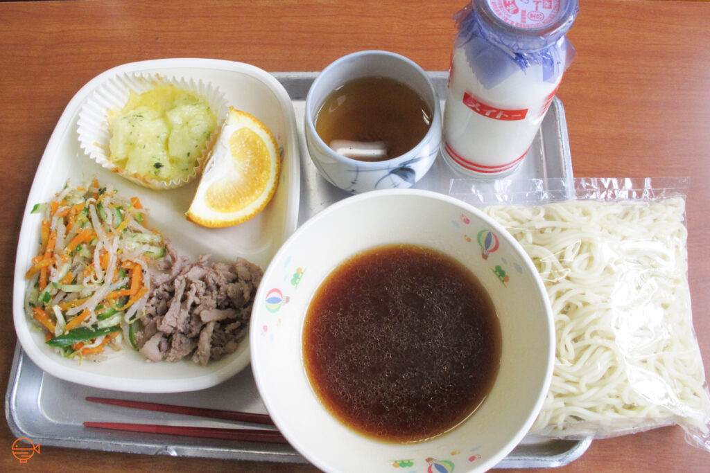 A small potato gratin, a slice of orange, a cold pickled salad and a serving of pork, next to a packet of cold noodles and soy-sauce based dipping sauce. Behind it is a hot cup of hojicha tea and a cold bottle of milk.
