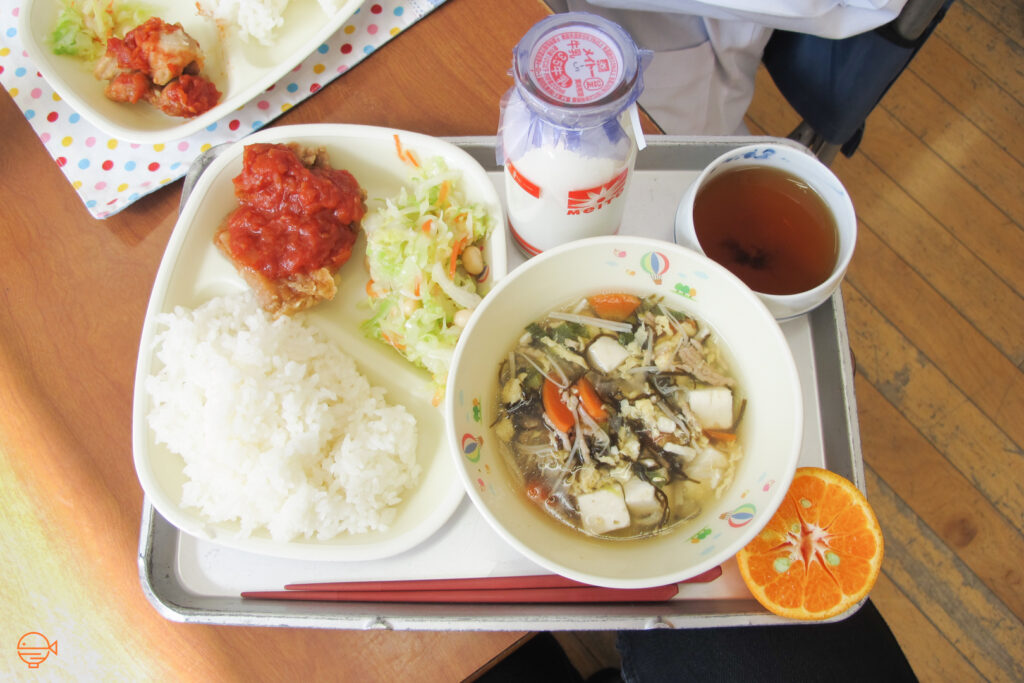 Fried fish with a tomato-based sauce, a cold pickled salad and a serving of rice. To the right is a large bowl of vegetable, tofu and pork soup, along with half an orange, a cup of hot hojicha tea and a bottle of cold milk.