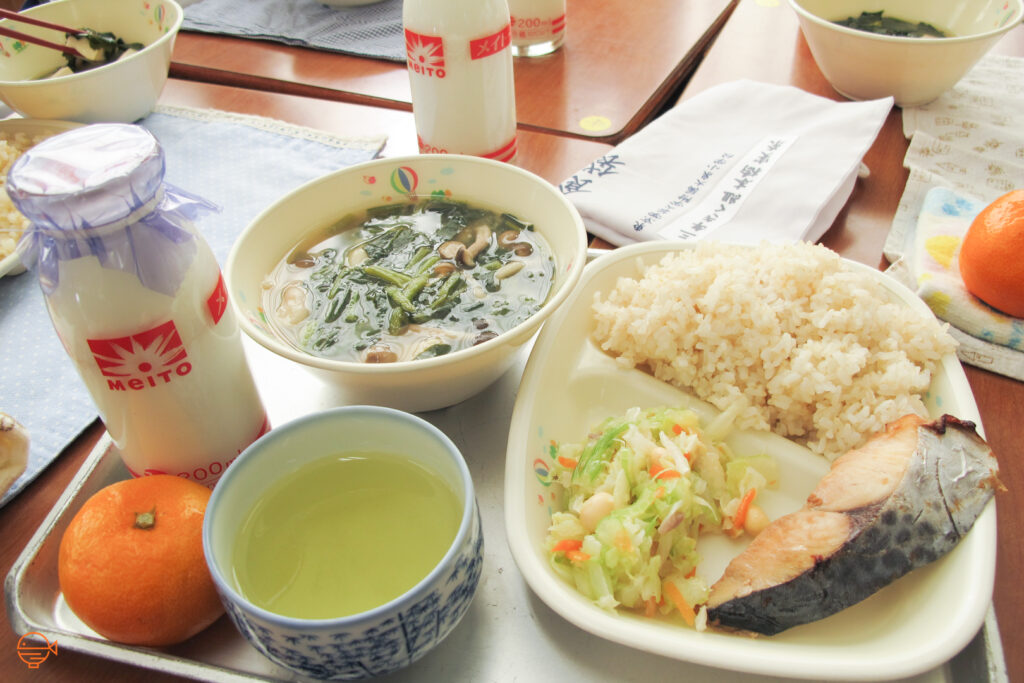 A serving of rice with a piece of salmon and a cold pickled salad. To the left is a hot bowl of soup filled with green vegetables and mushrooms, a cup of green tea, a mandarin and a bottle of cold milk.