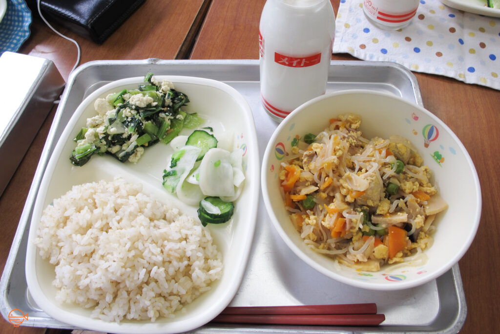 A serving of rice with a green vegetable and tofu salad, and pickled daikon radish and cucumber. To the right is a large bowl of glass noodles with vegetables and egg. Behind it is a bottle of cold milk.