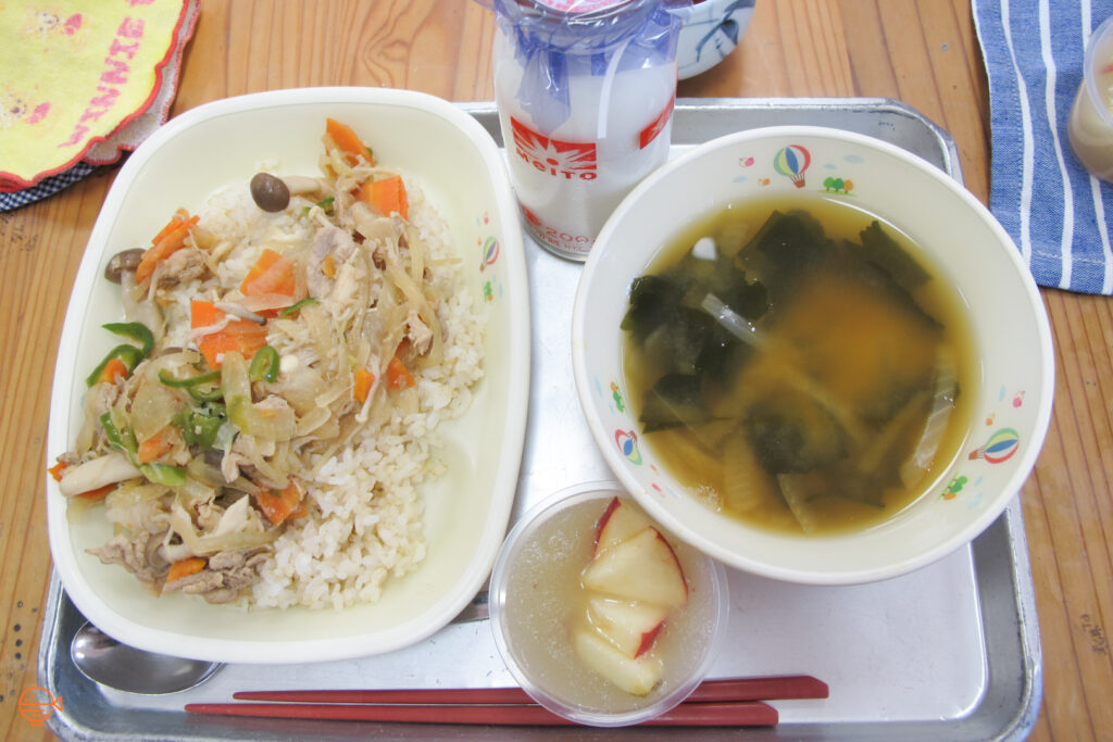 A serving of rice with a pork and vegetable stir fry. To the right is a bowl of miso soup with onion and wakame seaweed, and a serving of apple sauce with several pieces of fresh apple on top. At the back is a bottle of cold milk.