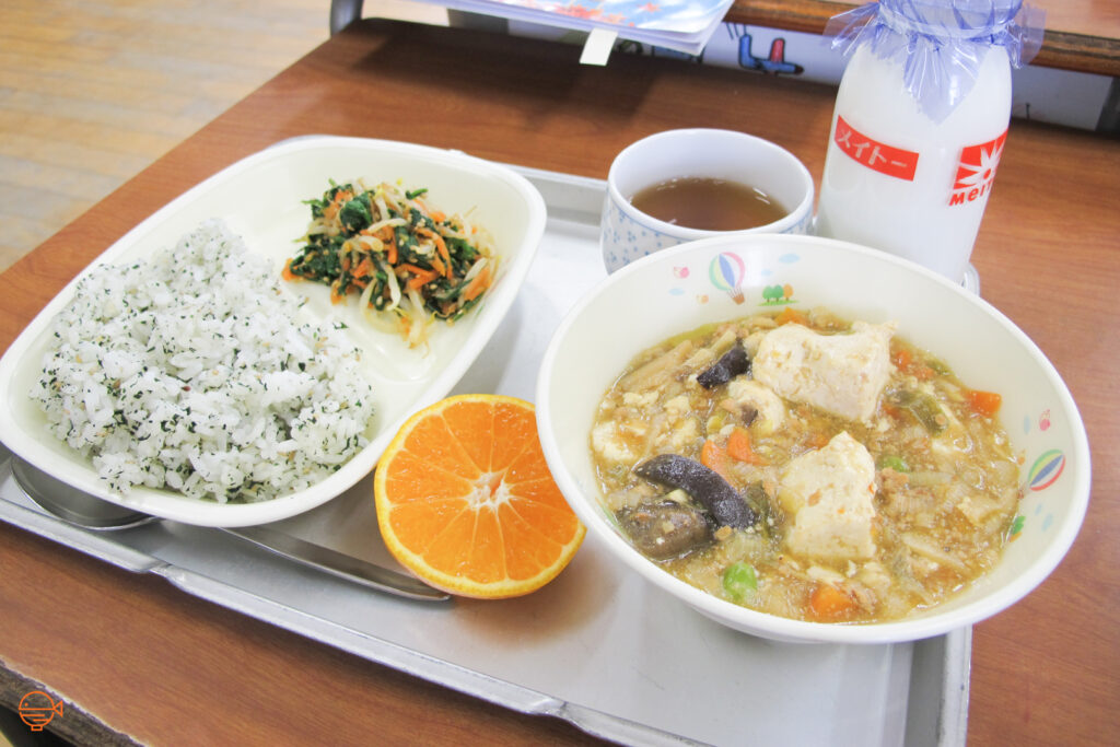 Seasoned rice with a cold pickled salad. To the right is a large hot bowl of soup filled with vegetables, tofu and pork. Sitting around it is half an orange, a hot cup of hojicha tea and a bottle of cold milk.
