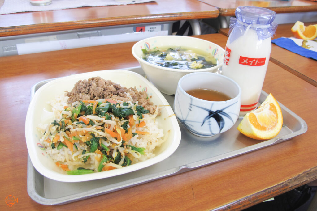 A large serving of rice with pork and mixed vegetables. To the right is a hot bowl of seaweed, egg and vegetable soup, a slice of orange, a hot cup of hojicha tea and a cold bottle of milk.