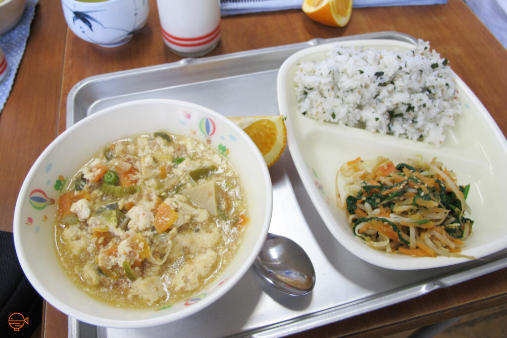 A large bowl of hot soup with tofu and vegetables. To the right is a serving of seasoned rice, a cold pickled salad and a slice of orange, with a hot cup of Japanese tea and cold milk at the back.
