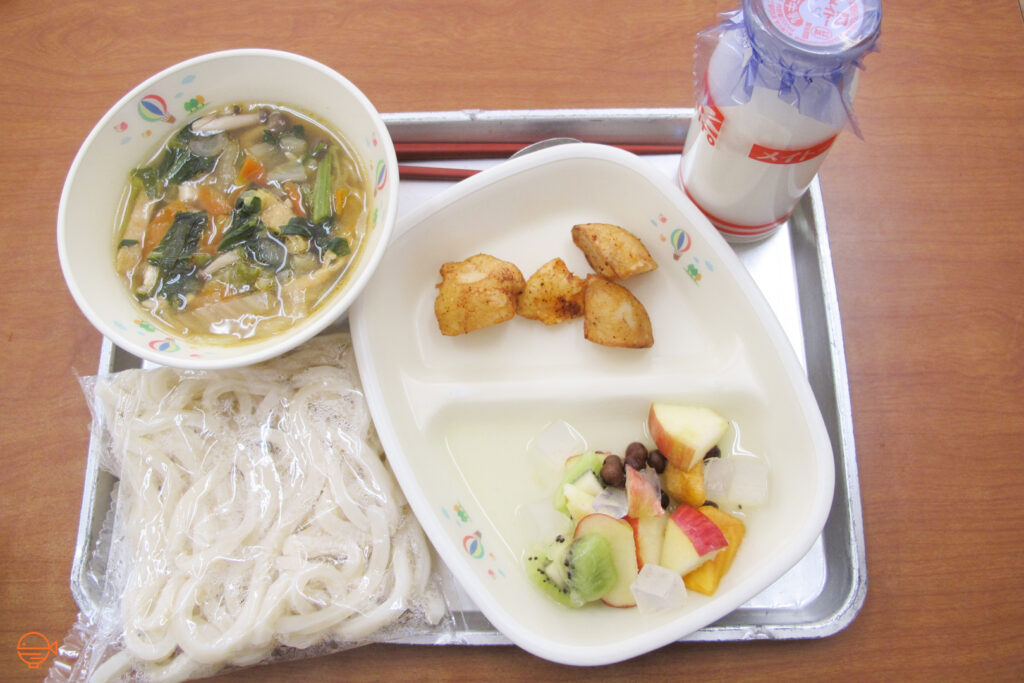 A packet of udon noodles and a hot bowl of vegetable soup. To the right is a small serving of fried potato and a fresh fruit salad with some almond jelly and red bean. Next to it is a bottle of cold milk.