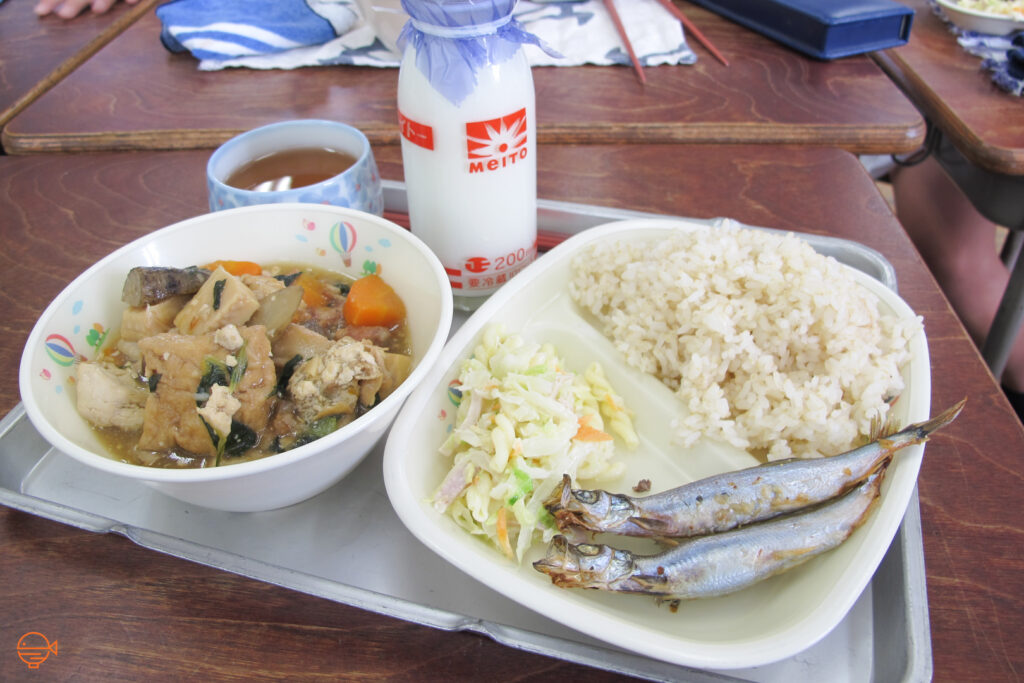 A serving of rice, two grilled smelt fish, a cold pickled salad, a bowl of soup packed with vegetables and tofu, a cup of hojicha tea and a bottle of cold milk.