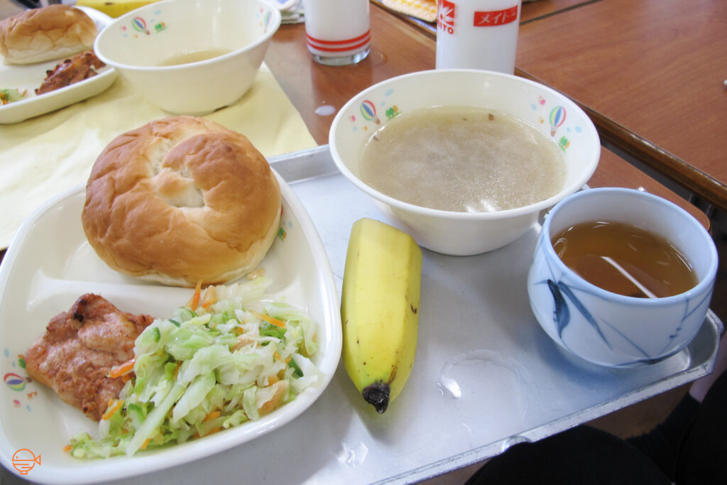A bread roll, pork and a cold pickled salad, along with a cloudy soup, half a banana, a hot cup of hojicha tea and a glass of cold milk.