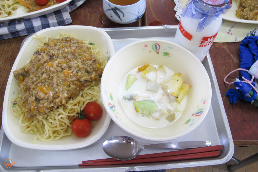 A large serving of egg noodles and a pork and vegetable filled sauce. To the left is a bowl of fruit salad and yoghurt, as well as a bottle of cold milk and a cup of hot hojicha tea to the back.