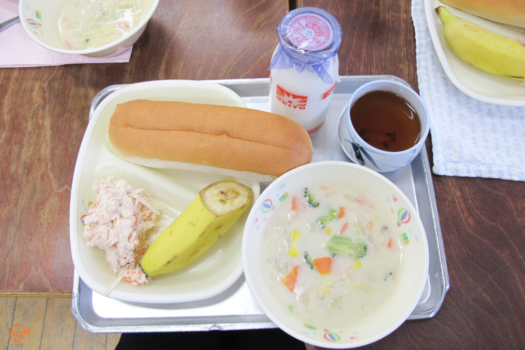 A hot dog style bun with a cold fish salad filling, along with a bowl of hot creamy soup with broccoli, carrot and corn. Also on the tray is half a banana, a hot cup of hojicha tea and a bottle of cold milk.