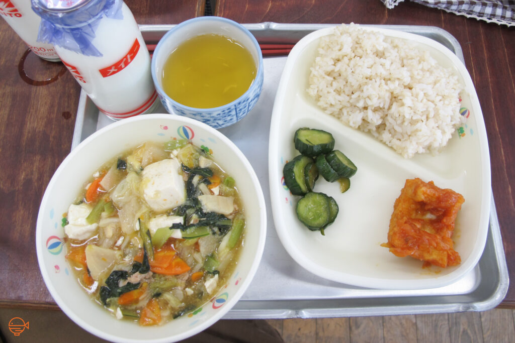 A large bowl of tofu, pork and vegetable soup, along with a serving of rice, fish, pickles, hot green tea and cold milk.