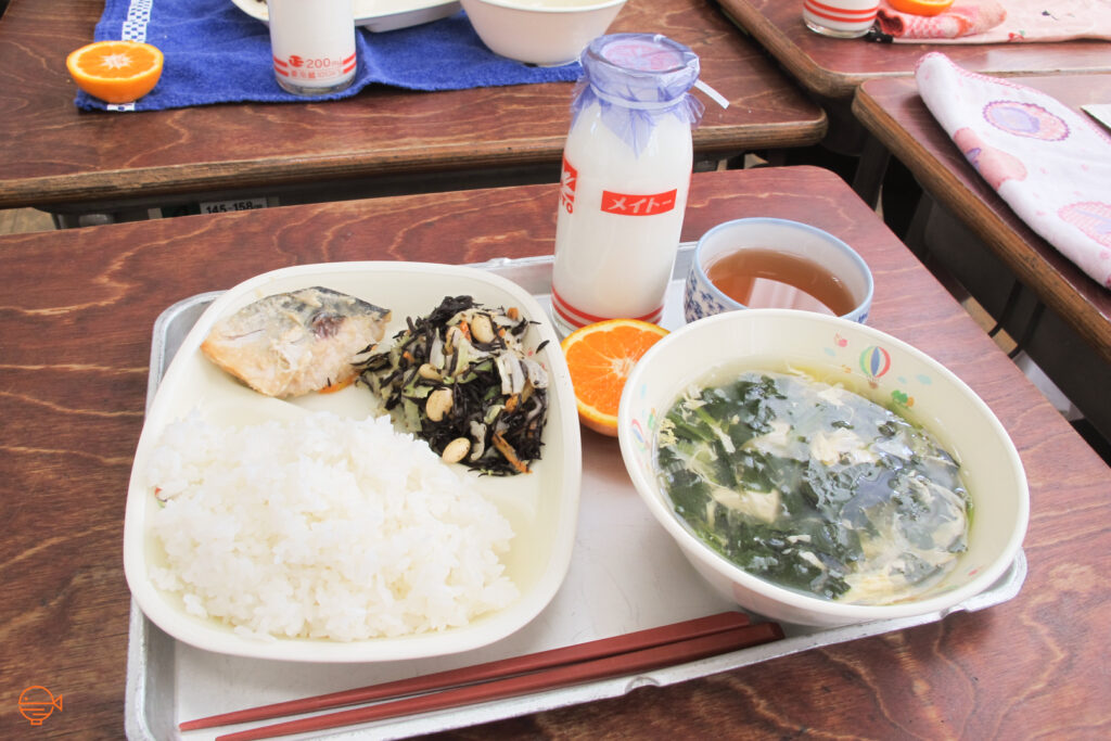 A serving of rice with a piece of fish and a Japanese side salad with wild brown seaweed, along with an egg and seaweed soup, half an orange, a cup of Japanese tea and a bottle of milk.