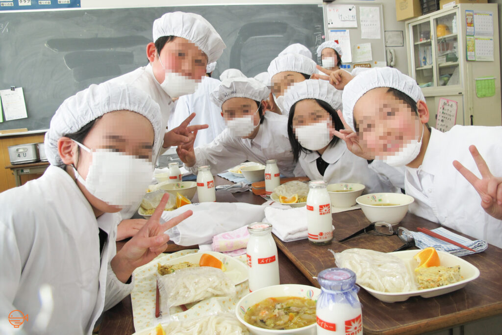 Japanese elementary school students in their white school lunch uniform.