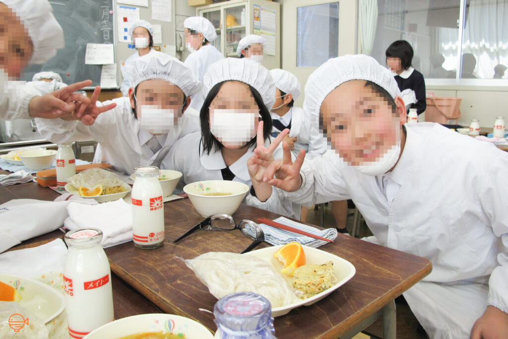 Japanese school students pose with their school lunches.