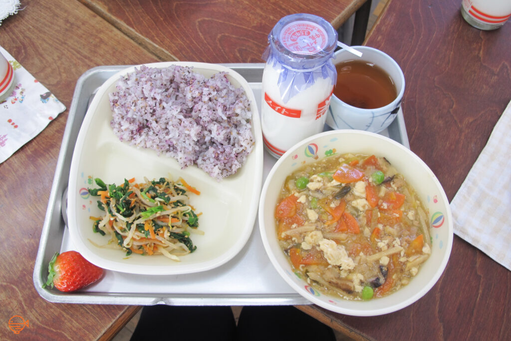 Seasoned rice, a pickled vegetable side salad, a strawberry, a bowl of tofu, pork and vegetable soup, along with a cup of roasted green tea and a bottle of cold milk.