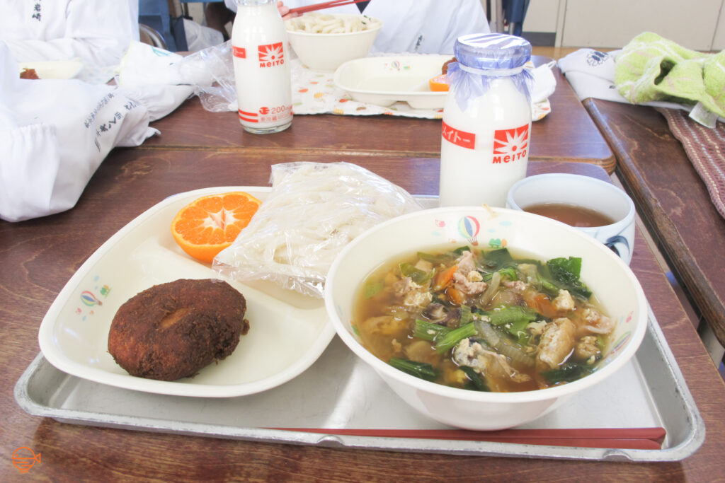A tofu and vegetable soup with udon noodles, along with a Japanese style croquette, half an orange, a cup of hot tea and a bottle of cold milk.
