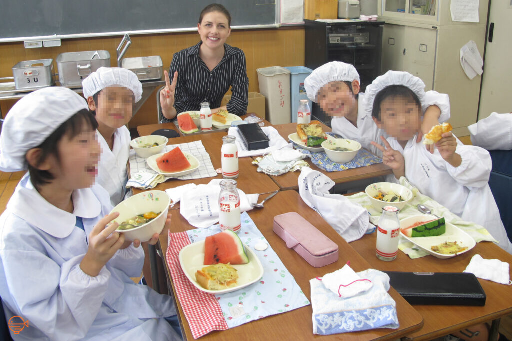 The author sits at a school lunch table with four students in their white school lunch uniforms who are partially through their meals and posing and smiling for the camera.