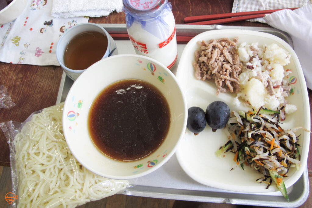 A packet of cold noodles and a soy sauce based dipping sauce, along with a hijiki seaweed and vegetable salad, potato salad with bacon, a serving of pork, two purple grapes, a cup of roasted green tea and a bottle of cold milk.