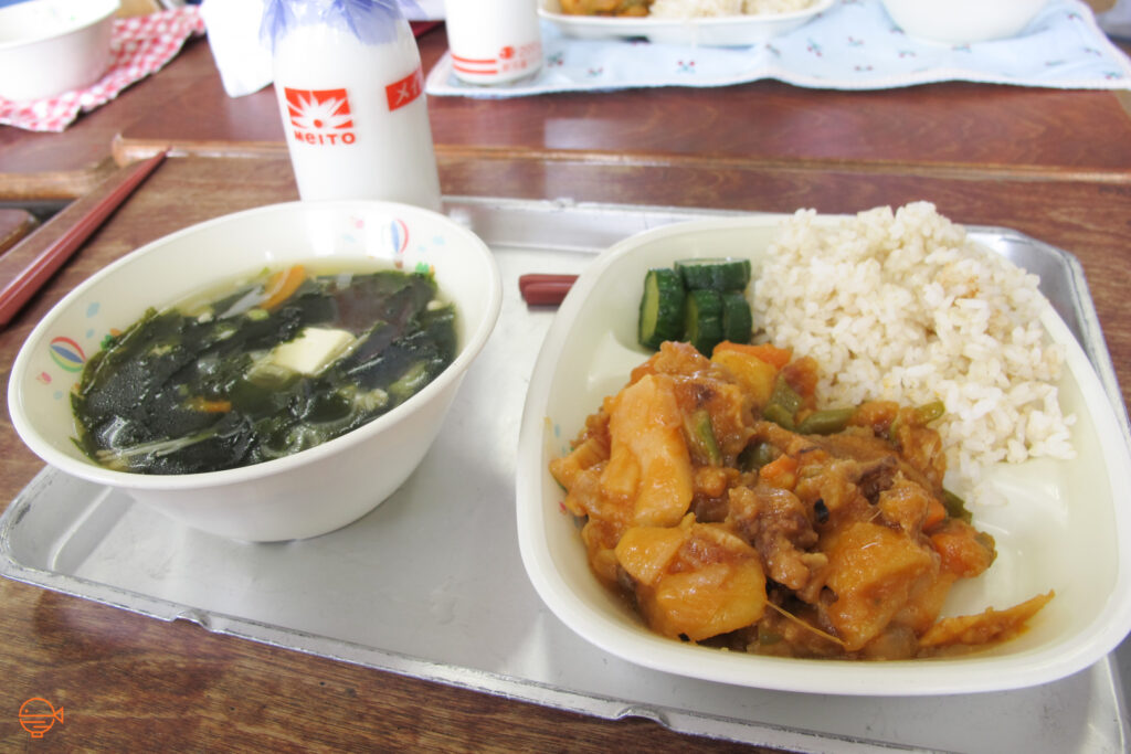 Sweet and sour pork with vegetables, rice and pickles, along with a bottle of milk.