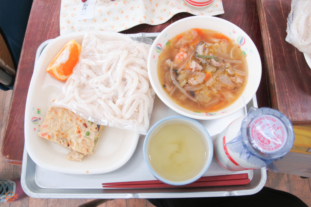 A prawn, pork and vegetable soup with udon noodles, a tofu and vegetable omelette, a slice of orange, a cup of green tea and a bottle of cold milk.