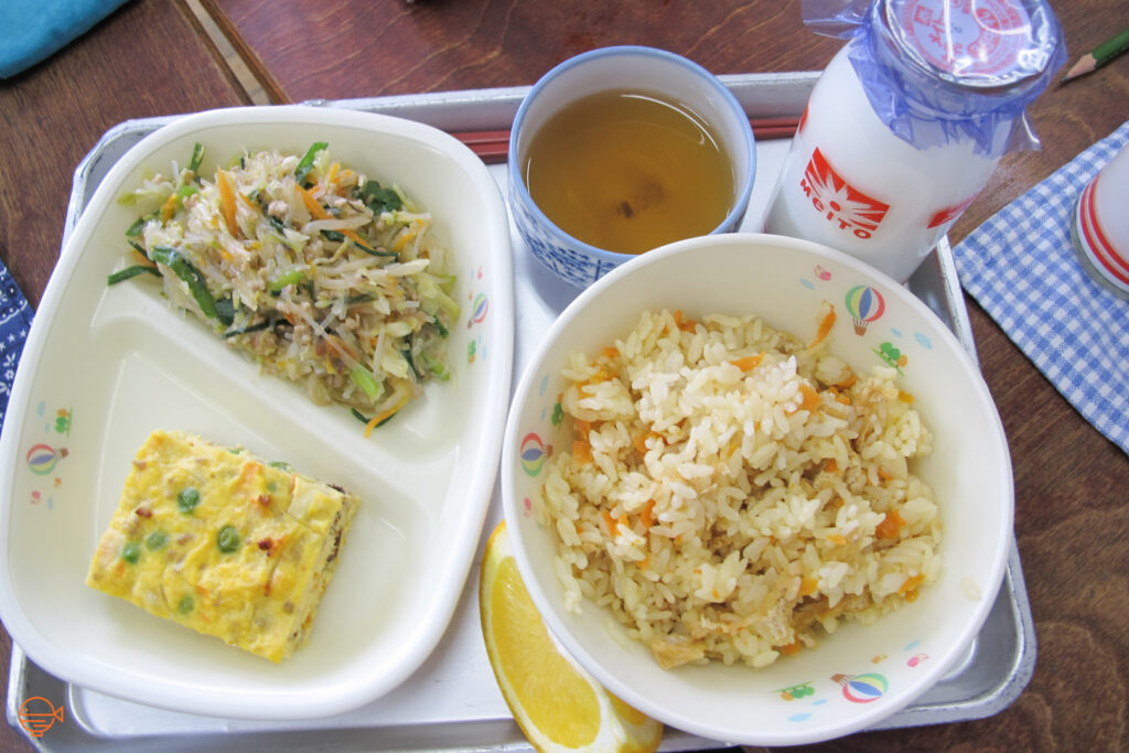 Seasoned rice with a pork and vegetable salad, a vegetable omelette, a slice of orange, a cup of roasted green tea and a bottle of cold milk.