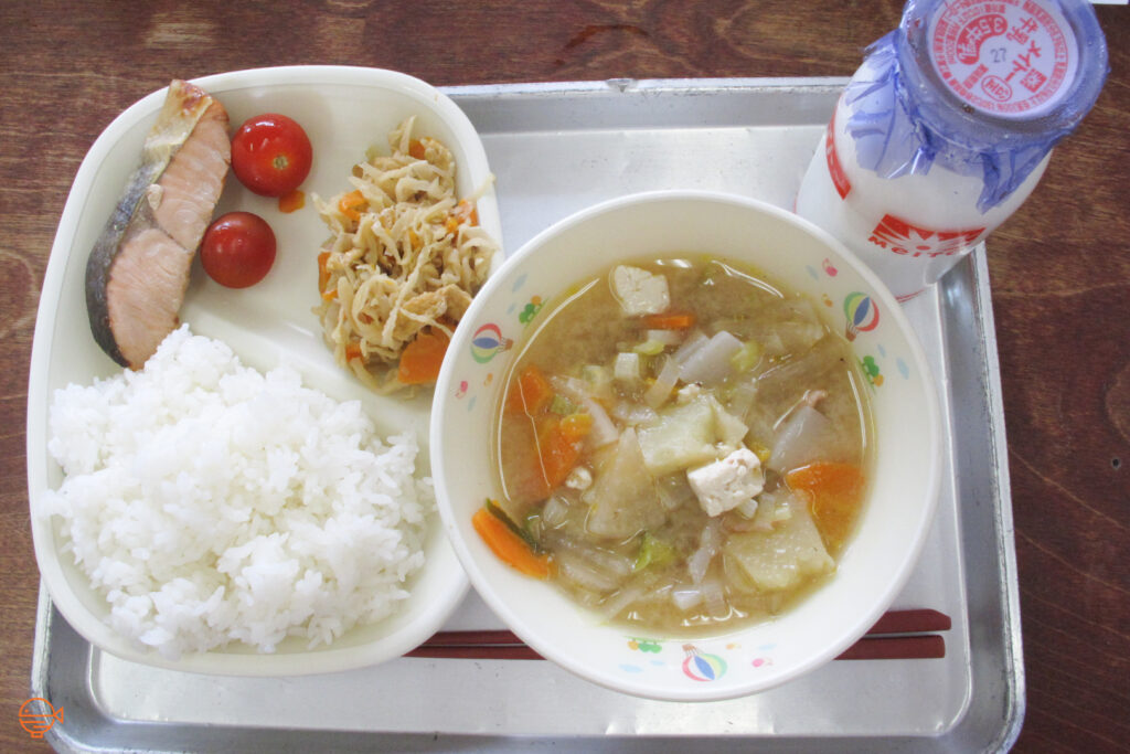 A serving of rice, fish, traditional side salad and two cherry tomatoes, along with a vegetable, tofu and pork soup, and a bottle of milk.