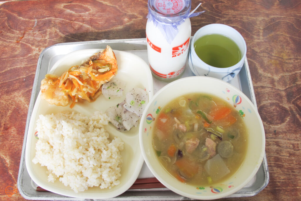 A serving of rice, battered fish with a sweet and sour topping, plus a side of pickles. To the right is a bowl of miso based pork and vegetable soup, and a bottle of milk and cup of green tea.