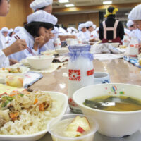 A Japanese school lunch sits on a tray in the foregound with a room full of elementary school students wearing whte hats and jackets tucking into their school lunch meals in the background.