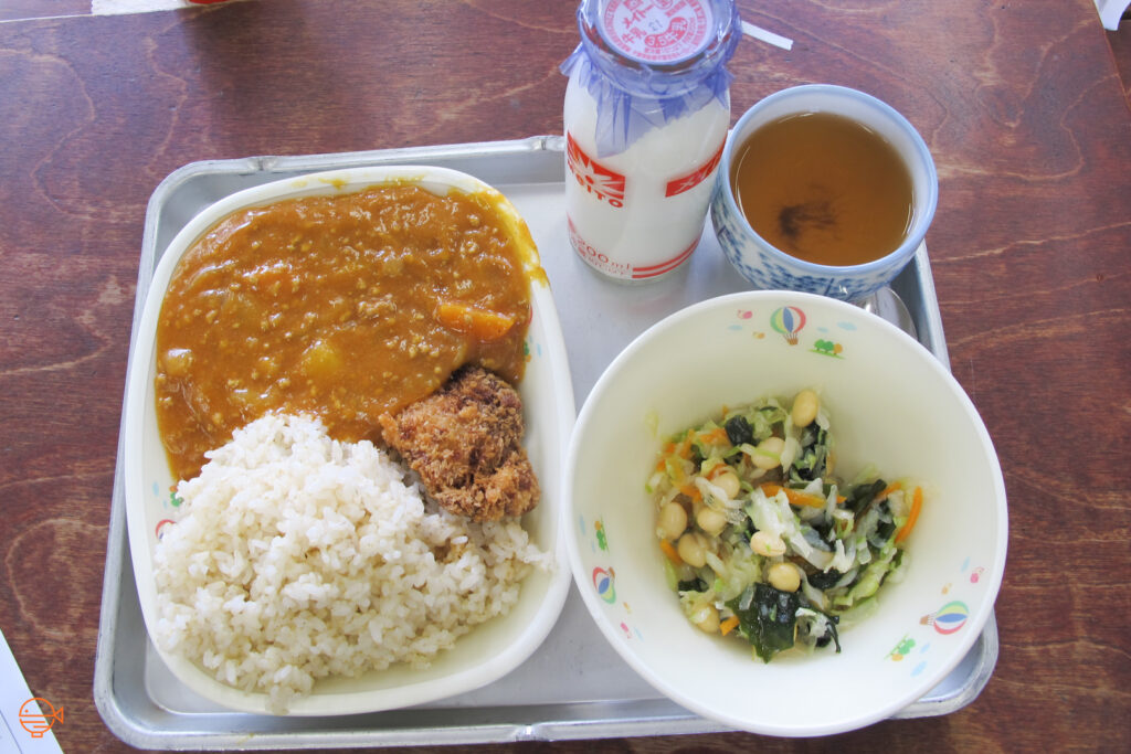 Curry with rice and fried pork, along with a cold pickled salad, a hot cup of roasted green tea and a bottle of cold milk.