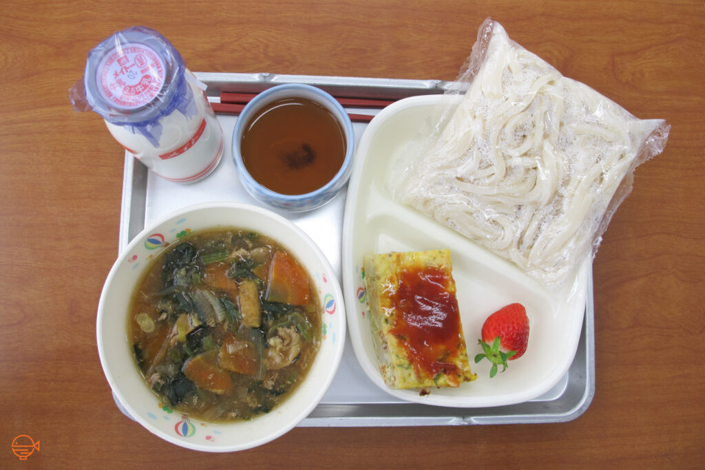 A pork and vegetable soup with udon noodles, along with a vegetable omelette with ketchup, a strawberry, a cup of roasted green tea and a bottle of cold milk.