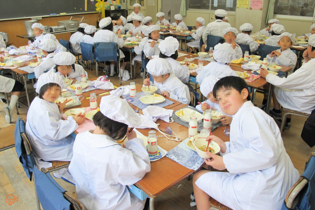 An elementary school class with their desks arranged into small groups, happily chat while eating school lunch, with a couple of them turning to pose for the camera.