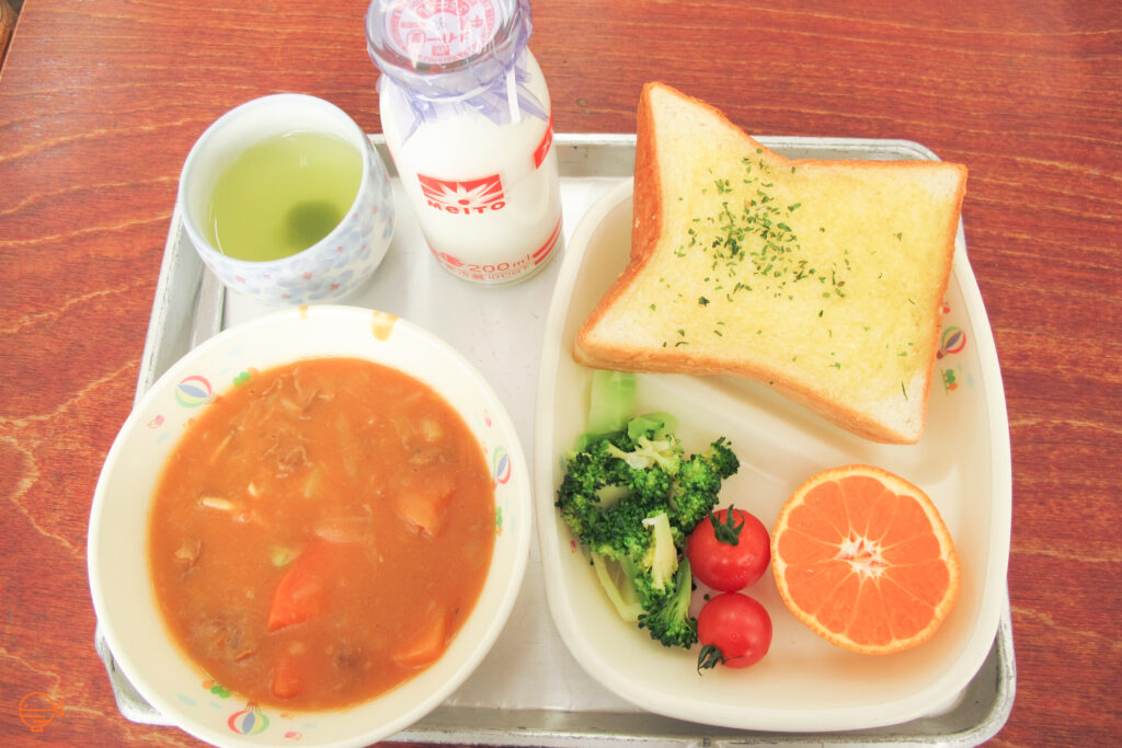 A tomato based meat and vegetable soup with garlic bread, broccoli, two cherry tomatoes, a piece of orange, a cup of green tea and a bottle of milk.