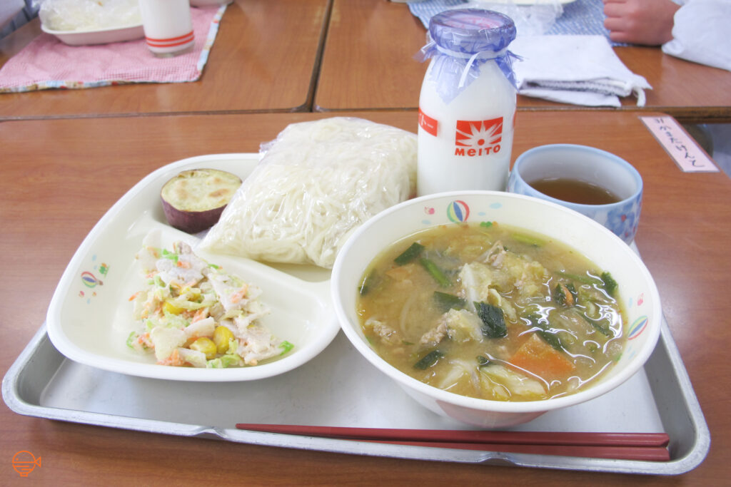 A miso based pork and vegetable soup with udon noodles, a vegetable and shirasu fish side salad and a piece of roast sweet potato, a cup of roasted green tea and a bottle of milk.