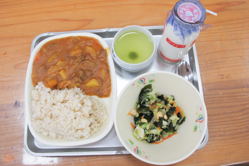 A beef and vegetable stew with rice, along with a cold pickled side salad, a cup of green tea and a bottle of cold milk.