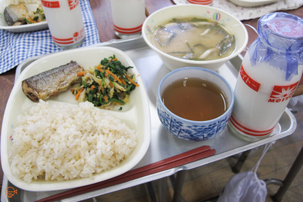 A serving of rice, fish and vegetables, along with a mushroom and seaweed soup, and a cup of roasted green tea and a bottle of milk.