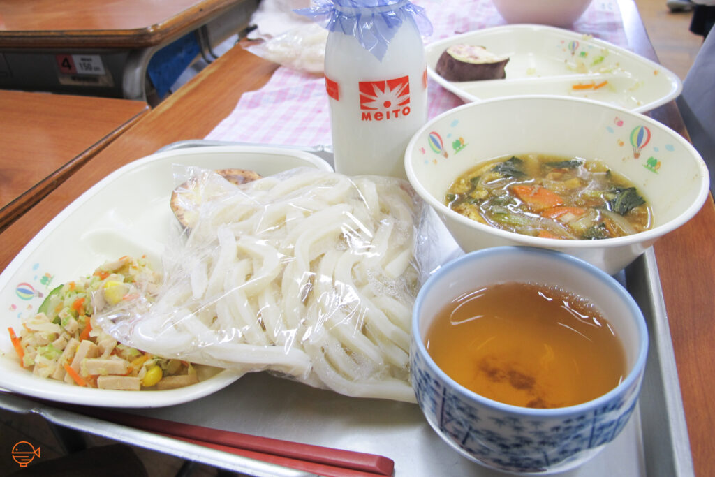 A vegetable soup with a packet of udon noodles, a vegetable and ham side salad, a piece of roasted sweet potato, a cup of roasted green tea and a bottle of cold milk.