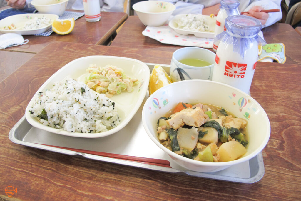 Seasoned rice with a cold pickled side salad, a large bowl of vegetable, tofu and pork soup, a slice of orange, a cup of green tea and a bottle of milk.
