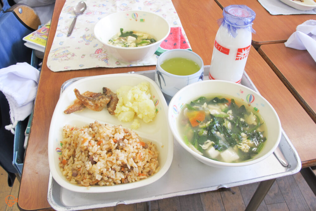 Tomato rice with fried fish and potato, a bowl of vegetable, seaweed and tofu soup, plus hot green tea and cold milk.