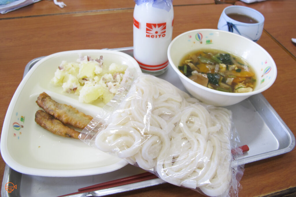 Vegetable, pork and tofu soup with udon noodles, two small fried fish, potato and bacon salad, roasted green tea and milk.
