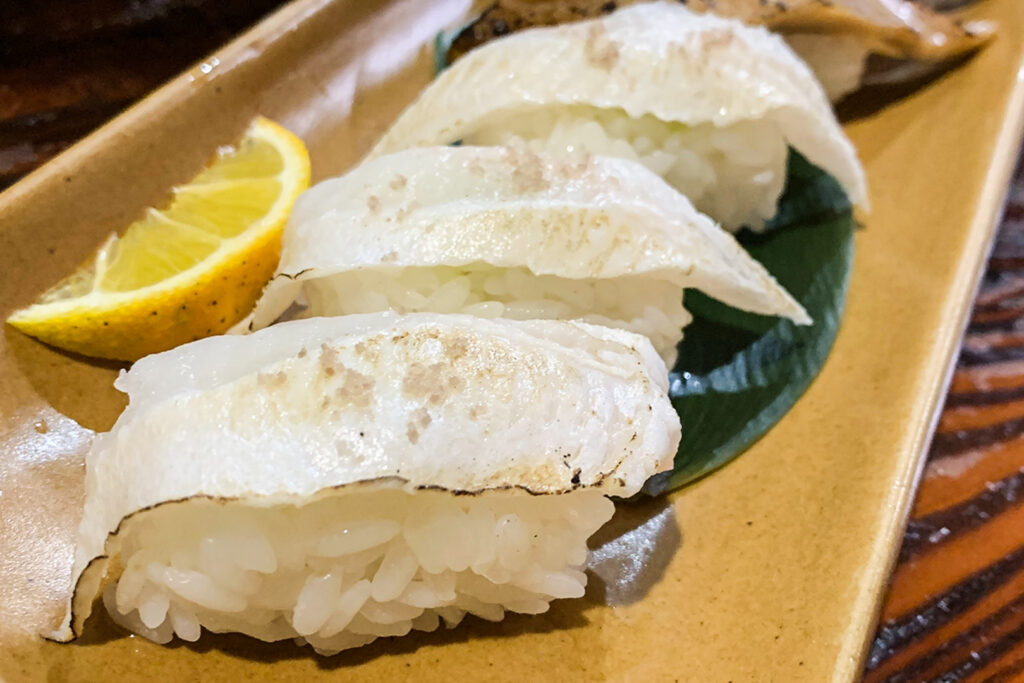 A serving of anago eel sushi, one of Tsushima Island's most famous foods, on a plate with a lemon wedge.