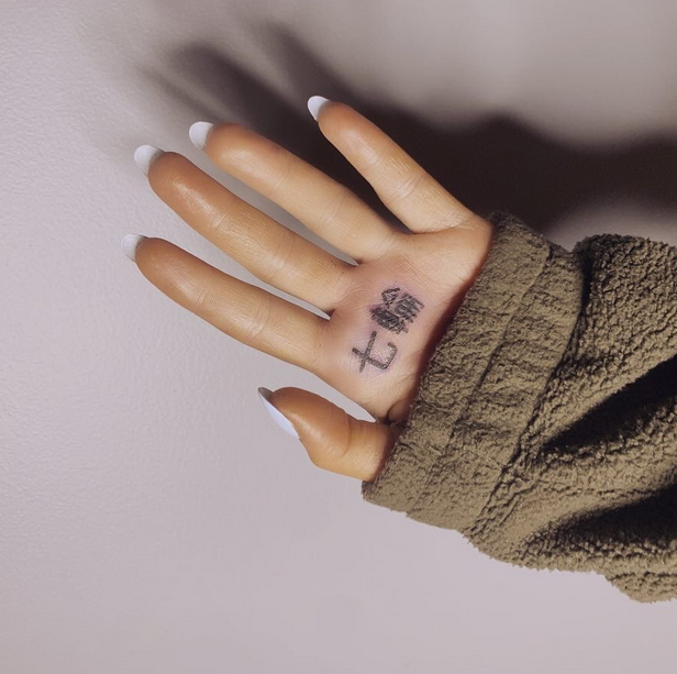 A photo posted to Ariana Grande's Instagram that shows her left palm facing the camera with the sleeve of her brown sweater covering the bottom part of her hand and a tattoo of two Japanese characters that say 'shichirin' (meaning a Japanese BBQ grill) at the top of her palm under her index and middle fingers.