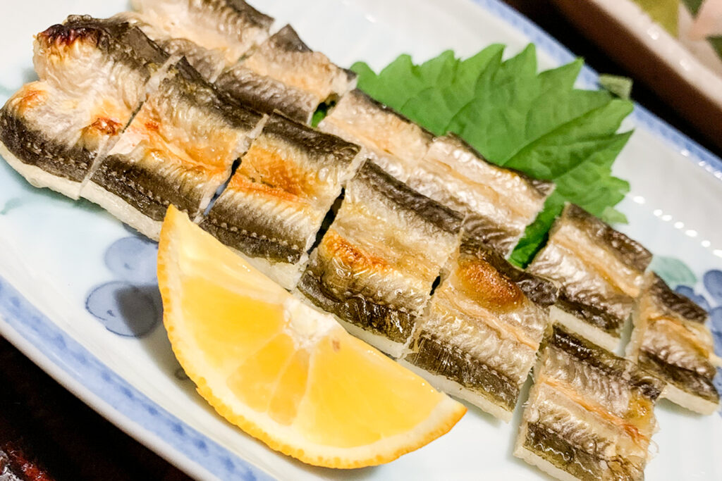 Grilled anago eel on a plate served with a shiso leaf and a wedge of lemon.
