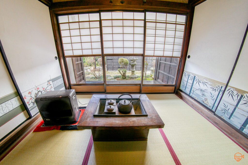 A hibachi sits in the middle of a traditional Japanese tatami room with a teapot and metal tongs inside the inner chamber.