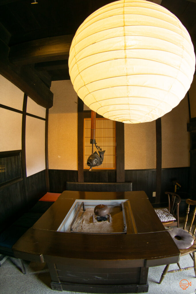 A wooden hibachi table with chairs around it. Set into the middle of the table is a metal box filled with warm ash and in the center is a small pile of burning charcoal with a tea pot on top.