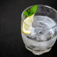 Shochu served mizuwari style in a clear glass with ice and water, along with some lemon and mint sits on a dark wooden counter top. © Hai Huynh.